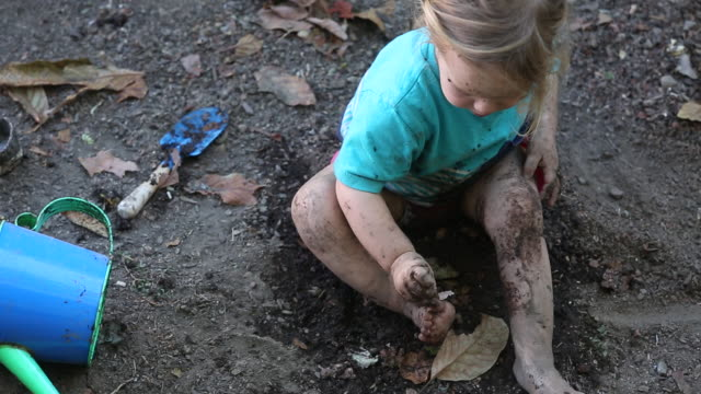 A young girl playing in the dirt outside with leaves and mud around her.