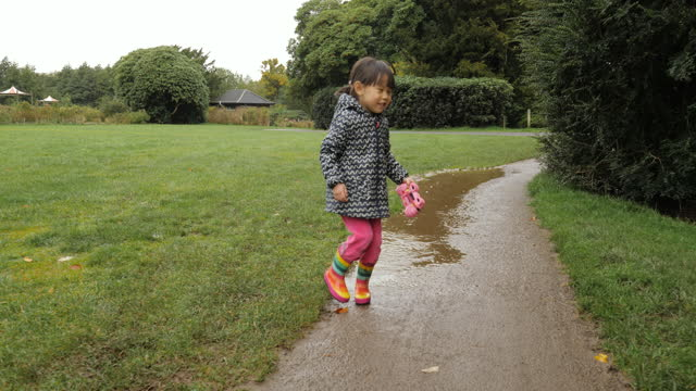 young girl playing mud puddle in the autumn countryside park - schoolgirl stock videos & royalty-free footage