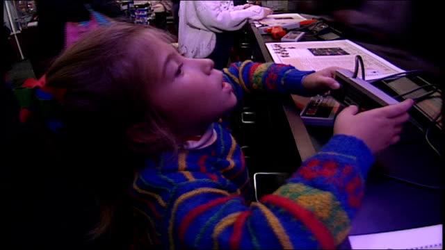 young girl playing nintendo - negozio di giocattoli video stock e b–roll