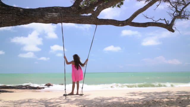 ws young girl playing on a swing by the sea - swing play equipment stock videos and b-roll footage