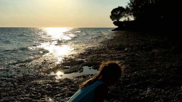 young girl playing on coastline during sunset - tanzania stock videos & royalty-free footage