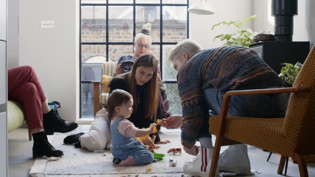 young girl playing on floor with family - part of a series stock videos & royalty-free footage