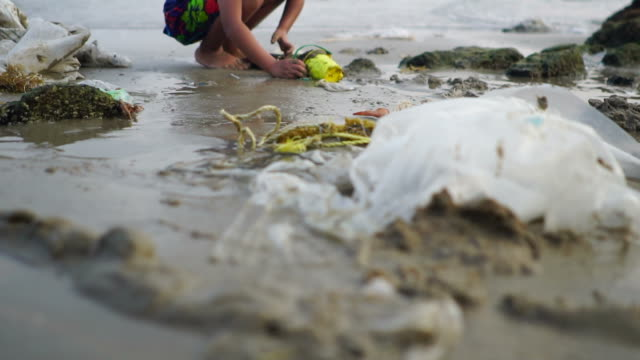 young girl playing on polluted garbage beach - developing countries stock videos & royalty-free footage