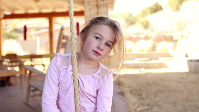 MS Young girl playing on rope swing / Lamy, New Mexico, United States