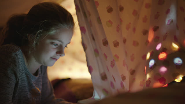 cu of young girl playing on tablet while inside pillow fort. - fortress stock videos & royalty-free footage