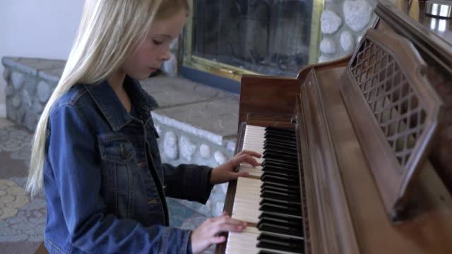 vídeos de stock, filmes e b-roll de ms young girl playing piano at home. - jaqueta jeans