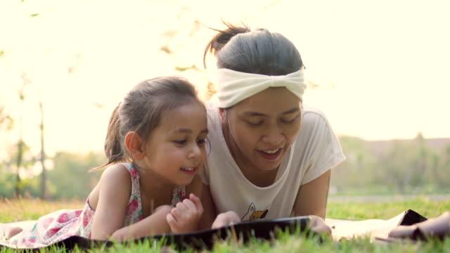 vídeos de stock, filmes e b-roll de jovem garota jogando telefone inteligente no parque com a família. - voz