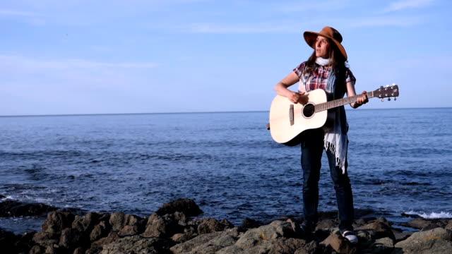 vídeos y material grabado en eventos de stock de una joven tocando la guitarra en la playa al amanecer - diapasón instrumento de cuerdas