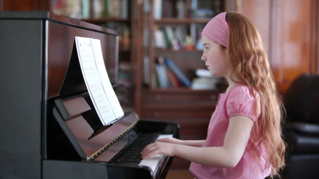 young girl playing the piano - piano stock videos and b-roll footage