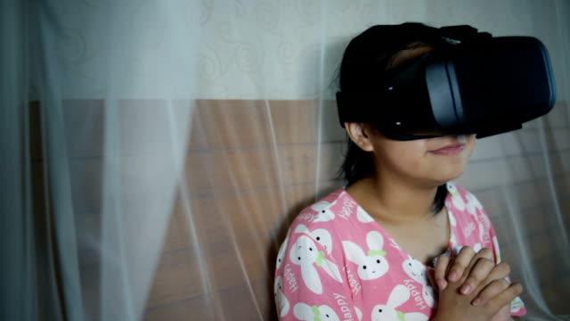 若い女の子がベッドの上に vr を再生 - ヘッドボード点の映像素材/bロール