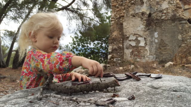 young girl playing with sticks by old buildings - mid length hair stock videos & royalty-free footage