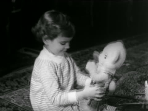 vidéos et rushes de b/w 1960 young girl playing with stuffed teddy bear at christmas / newsreel - cadeau de noël