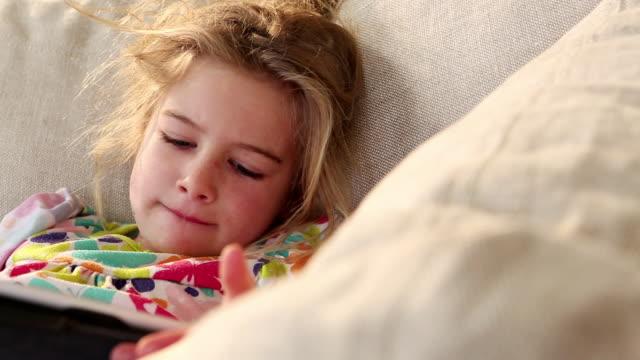 vídeos y material grabado en eventos de stock de ms pan young girl playing with tablet on sofa / lamy, new mexico, united states - nativo digital