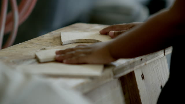 Young girl playing with wood pieces in the wood shop.