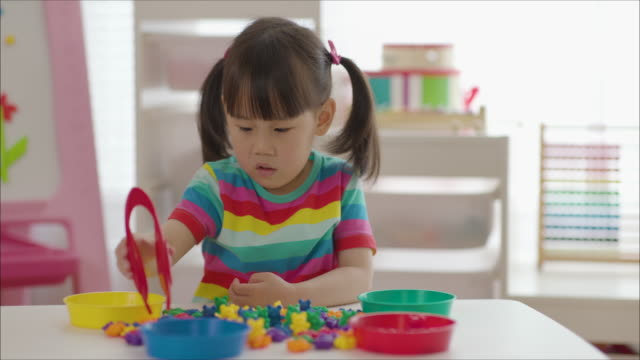 young girl plays for colour sorting and fine motor skill for home schooling - preschool student stock videos & royalty-free footage
