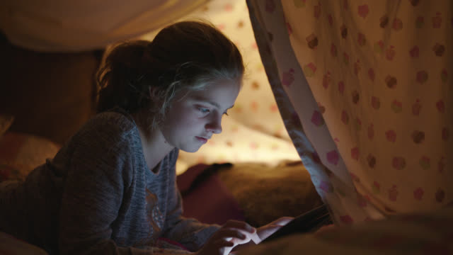 young girl plays games on her tablet while inside pillow fort. - blanket stock videos & royalty-free footage