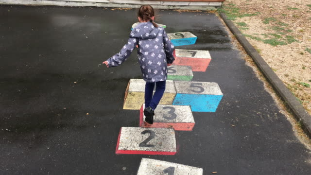 Young girl plays Hopscotch in the playground