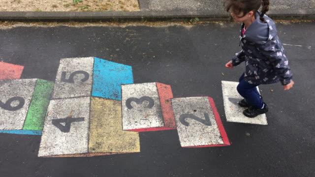 vídeos de stock e filmes b-roll de young girl plays hopscotch in the playground - equipamento de parque infantil