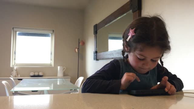 Young Girl Plays on Mobile Phone