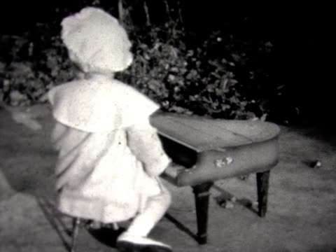 1934 young girl plays toy piano