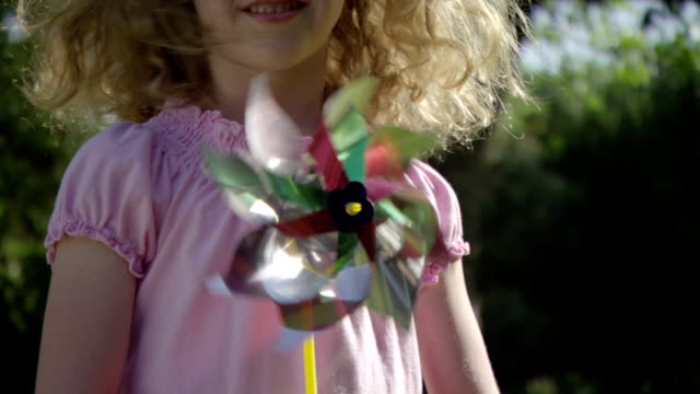 a young girl plays with a pinwheel. - windrad stock-videos und b-roll-filmmaterial