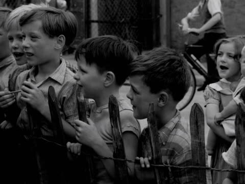 young girl points to a sign on the door of a youth club canteen that says only girls are allowed in. a group of boys are unimpressed. 1957. - only boys stock videos & royalty-free footage