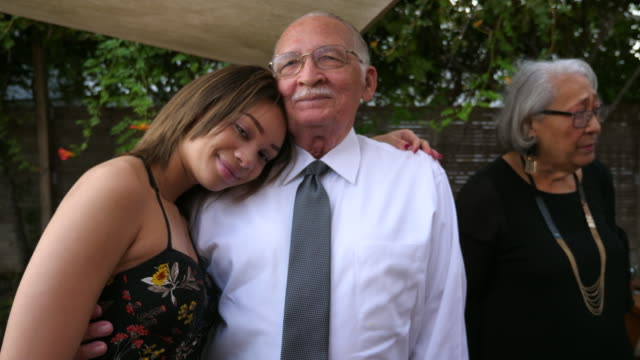 vídeos de stock e filmes b-roll de ms young girl posing for picture with grandfather after family dinner party - teenage girls