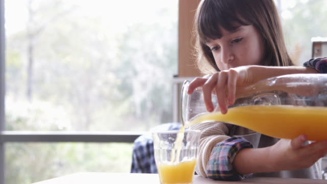 vídeos y material grabado en eventos de stock de young girl pours and drinks a glass of freshly squeezed orange juice - zumo de naranja