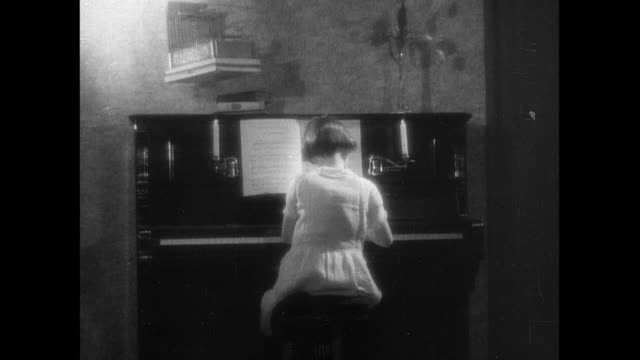 montage young girl practicing at piano, sign over front door, chimney with smoke, pet bird in cage, wedding photo on wall, and housewife setting table / england, united kingdom - 1934 stock videos & royalty-free footage