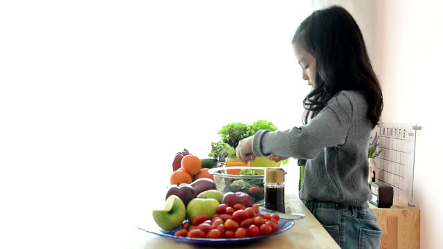 young girl preparing food in the kitchen - making salad stock videos & royalty-free footage