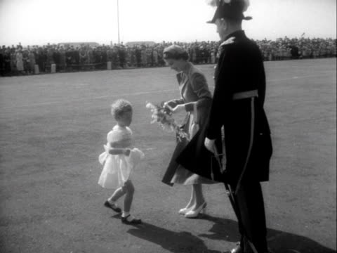 a young girl presents the queen with a bouquet of flowers on the runway of aldergrove airport at the start of the queen's state visit to northern... - composizione di fiori video stock e b–roll