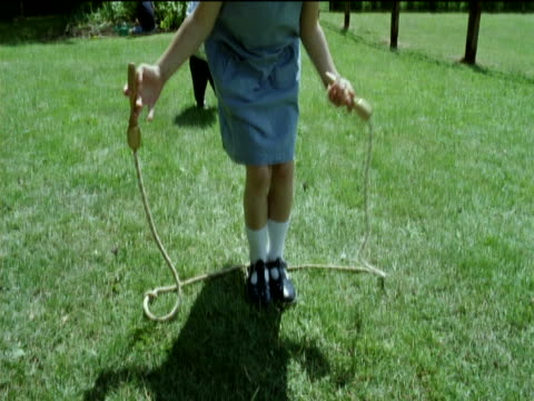 young girl pulls her socks up and runs away skipping with a skipping rope in the garden, her younger brother plays with a football - femmina con gruppo di maschi video stock e b–roll