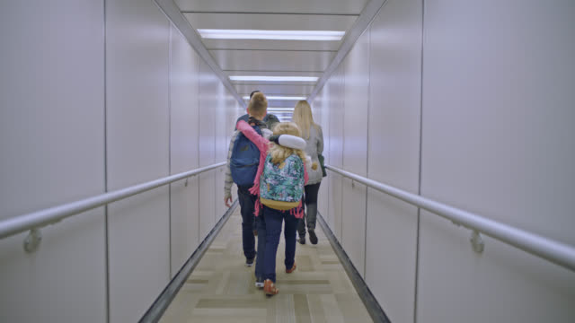 slo mo. young girl puts arm around older brother as family of four walks down jet bridge. - fluggastbrücke stock-videos und b-roll-filmmaterial