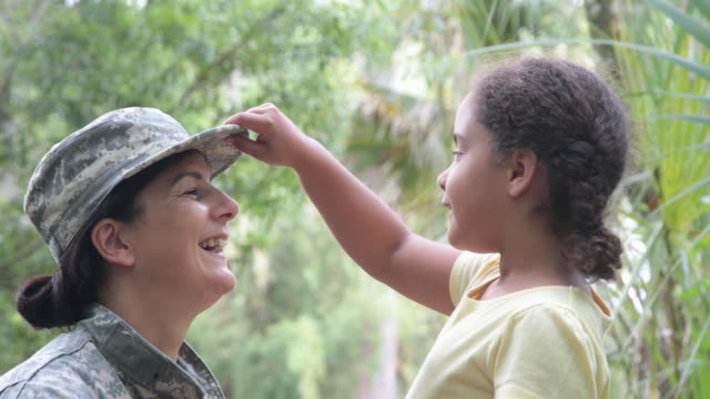 vídeos de stock, filmes e b-roll de cu young girl puts on military mum's hat - 2016