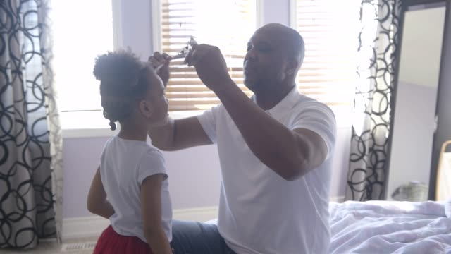 young girl putting tiara on father's head. - tiara stock videos & royalty-free footage