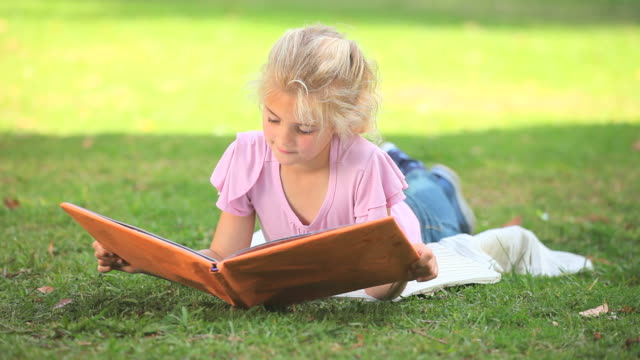 young girl reading a book outdoors / cape town, western cape, south africa - legs crossed at ankle stock videos & royalty-free footage