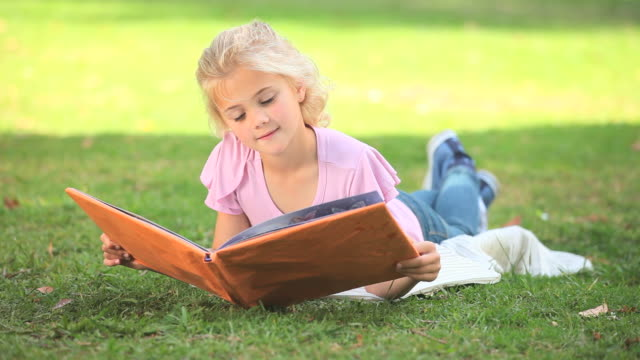 young girl reading a book outside / cape town, western cape, south africa - legs crossed at ankle stock videos & royalty-free footage