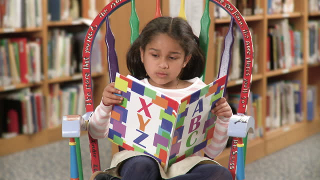 young girl reading alphabet book in school library - kindergartengebäude stock-videos und b-roll-filmmaterial