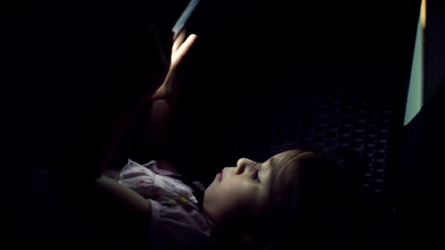 Young girl reading and using tablet