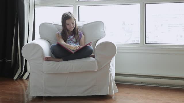ms young girl reading in armchair / montreal, quebec, canada - korslagda ben bildbanksvideor och videomaterial från bakom kulisserna