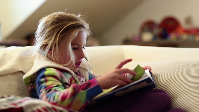 vidéos et rushes de ms young girl reading storybook in her room / lamy, new mexico, united states - lit ameublement
