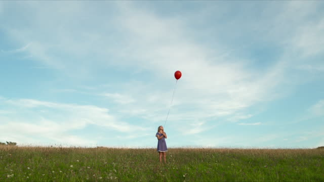 MWS young girl releasing balloon in field tilt up