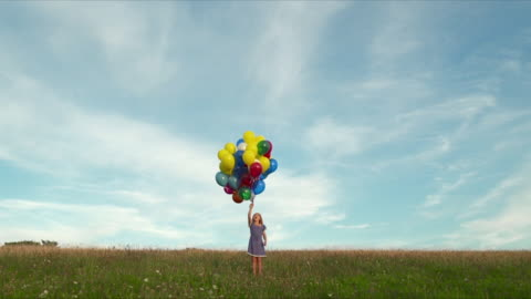 mws young girl releasing  bunch of  multi coloured balloons in field  - float stock videos & royalty-free footage