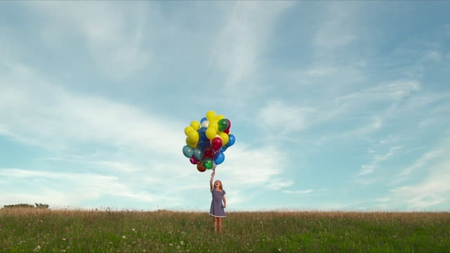 vídeos y material grabado en eventos de stock de mws young girl releasing  bunch of  multi coloured balloons in field  - flotando en el aire