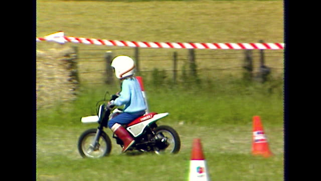 young girl rides a minibike around traffic cones on grass; 1984 - motorbike stock videos & royalty-free footage