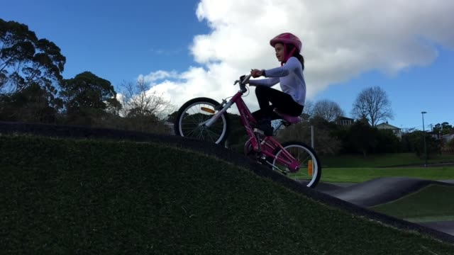 Young Girl Rides Bicycle on Obstacle Course