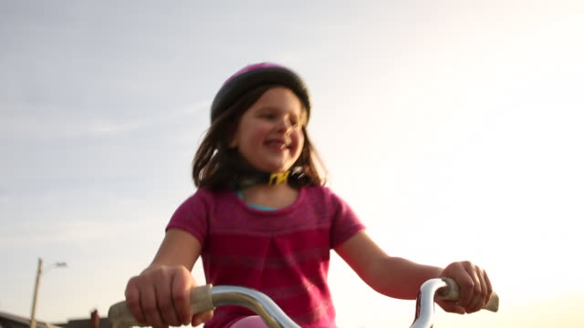 a young girl riding her bike outside on a sunny day near the beach. - オレゴン沿岸点の映像素材/bロール