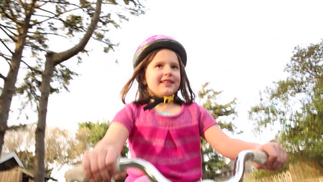 A young girl riding her bike outside on a sunny day near the beach.