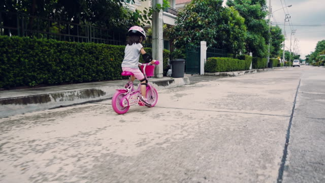 A young girl riding her bike outside on a sunny day near the home, Thailand