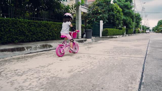 Ein junges Mädchen mit ihrem Fahrrad außerhalb an einem sonnigen Tag in der Nähe der Heimat Thailand